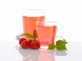 Glasses of raspberry-flavored drink and fresh raspberries